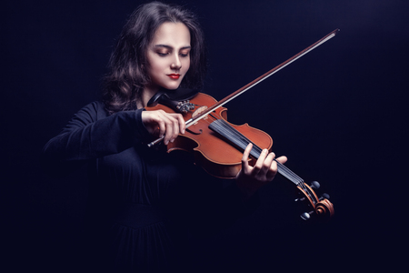 Young woman playing the violin against a dark background. Studio photo Stock Photo