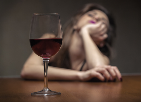 Woman in depression, drinking alcohol. Focus on the glass