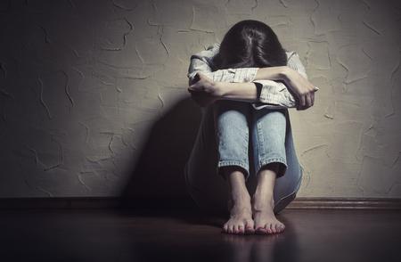 Giovane donna triste seduta da sola sul pavimento in una stanza vuota