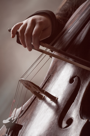 soloist: Close-up of a persons hand playing classical music on a violoncello. Musical concept Stock Photo