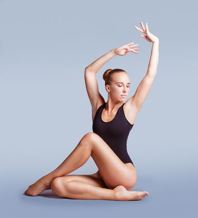 Schöner Turner des jungen Mädchens in einem schwarzen Badeanzug zeigt ein gymnastisches Element. Atelieraufnahme Kunstgymnastik