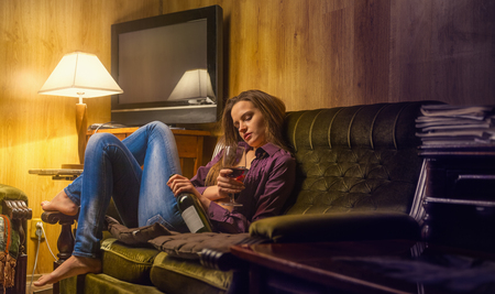 Lonely young woman with a drink rests on the couch in her office