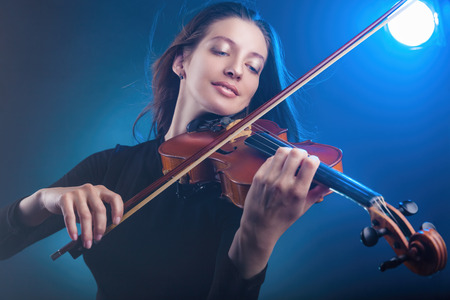Beautiful young woman playing the violin on dark blue background. Studio shot