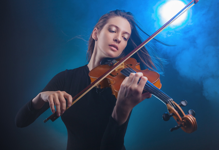 Beautiful young woman playing the violin on dark blue background. Fog in the background. Studio shot