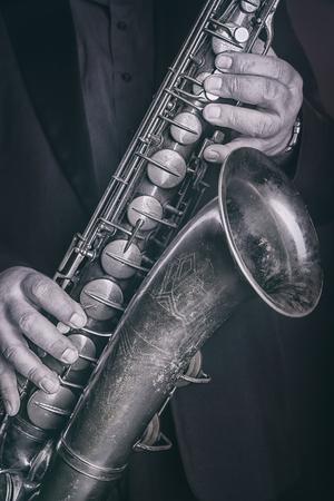 Saxophone player jazz music instrumental. Alto sax musical instrument close up. Black and white image Stock Photo