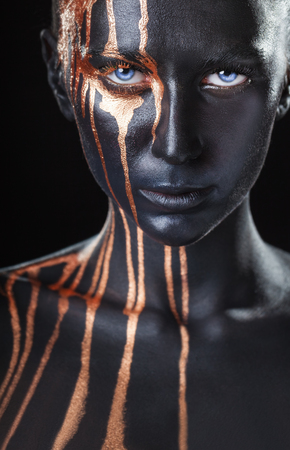 Art fashion makeup. An amazing woman with black makeup and leaking gold paint Stock Photo