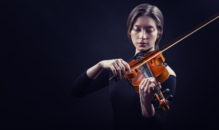 Beautiful young woman playing the violin against a black background Stok Fotoğraf