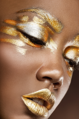 Young African American woman with silver and gold make-up on a black background