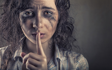 Domestic violence concept. Young woman with finger over her mouth