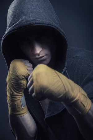 Martial arts fighter in the hood over black background