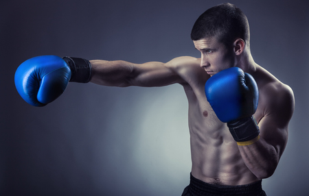 Boxing concept. Boxer with boxing blue gloves on a dark background. Studio shot Stock Photo