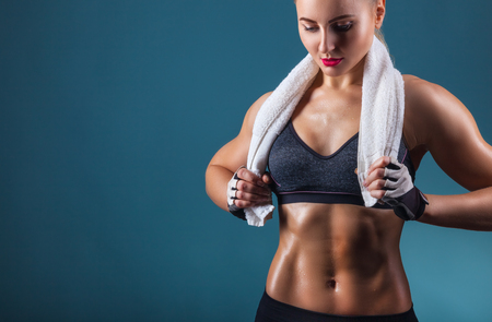 Young sports woman after workout with towel on his shoulders on a dark background Stock Photo