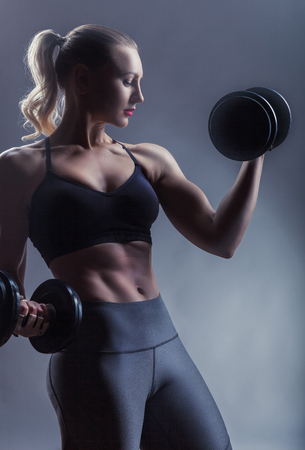 Beautiful fitness woman with heavy weights against a grey background. Sport concept