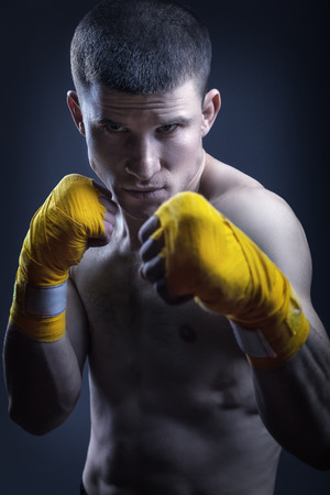 Young man in yellow straps shows the different strikes in the studio over black background
