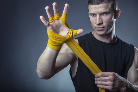 Close-up of a strong boxer putting on yellow straps and getting ready to fight