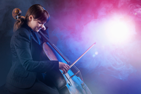 Close-up of cellist playing classical music on cello. Fog in the background. Studio shot