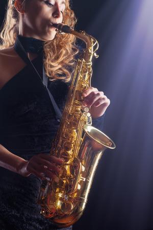 Saxophone player. Woman with saxophone. Studio shot