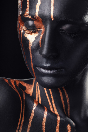 Creative makeup. Closeup portrait of woman an amazing woman with black makeup and leaking gold paint Stock Photo