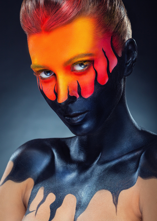 Portrait of a woman with black orange make-up and black tongues of flame on a black background. Studio shot