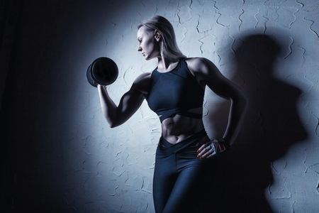 Fitness young woman with heavy weights. Sports concept