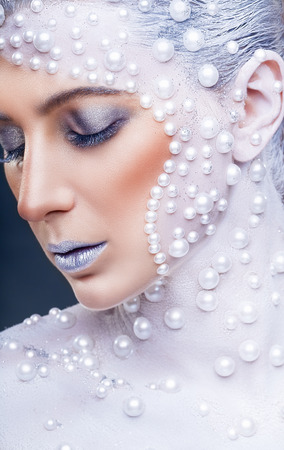 Fantasy makeup. Closeup portrait of a beautiful woman with creative make-up with white pearls Stock Photo