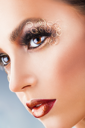 Fashion makeup. Close-up face of a young woman with fashion makeup