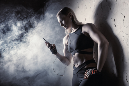 Young woman listening to music on headphones before workout in the smoke Stock Photo