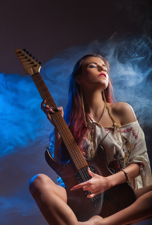 Sexy girl with electric guitar in blue smoke. Studio shot