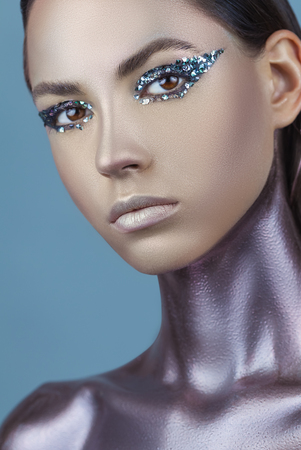 Portrait of a young woman with makeup fashion. Sparkly smokey eyes. Neck and chest are covered with metallic make-up