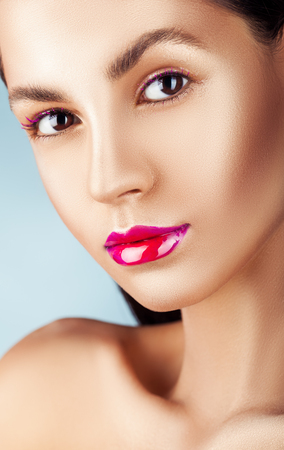 Close-up face of a beautiful woman with pink fashion make-up. Glossy transparent shadows and bright pink lips Standard-Bild - 117341064