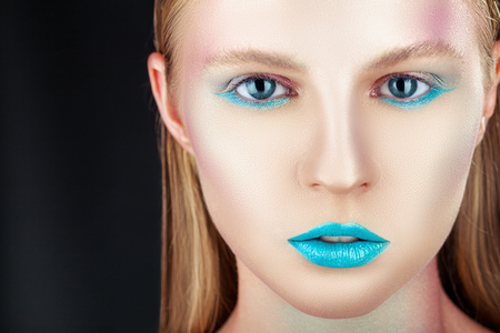 Fashion makeup. Close-up of a young woman with turquoise makeup on a black background Standard-Bild - 117341162