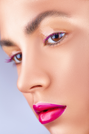 Close-up face of a beautiful woman with pink fashion make-up. Glossy transparent shadows and bright pink lips Standard-Bild - 116739727