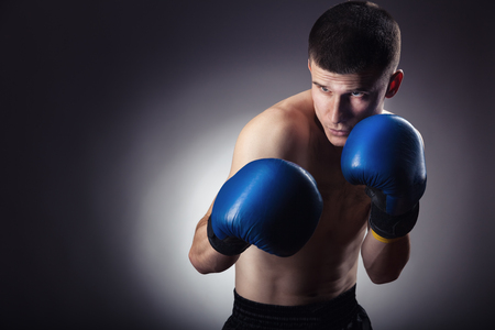 Boxing concept. Boxer with an aggressive look in blue boxing gloves before a fight against a black background Stock Photo