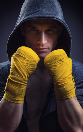 Muscular boxer in a hood with strong hands and clenched fists on a black background