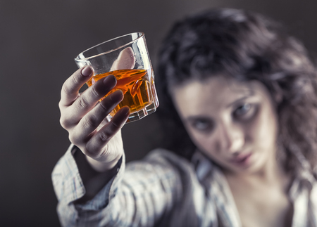 Young woman in depression, drinking alcohol on dark background. Focus on the glass Standard-Bild - 118541651