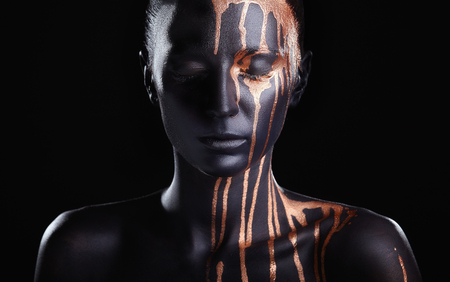 Art fashion makeup. An amazing woman with black makeup and leaking gold paint Imagens