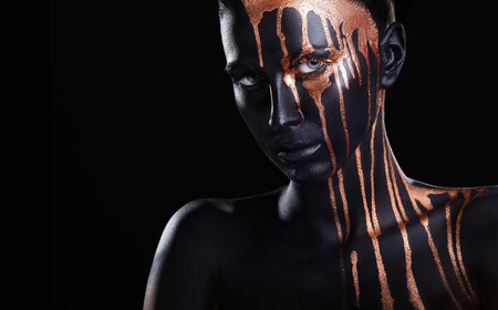 Art makeup. An amazing woman with black makeup and leaking gold paint