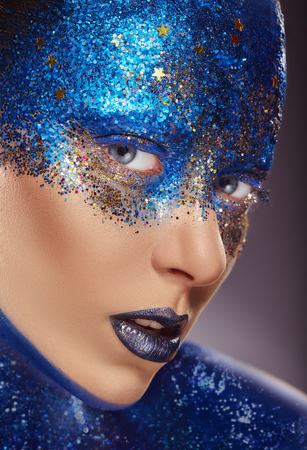 Close-up of a young woman with make-up made of blue sequins with stars. Art fashion Standard-Bild - 118454372