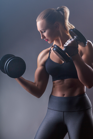 The concept of health and sport. Beautiful sporty woman with heavy weights