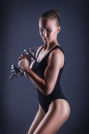 Sporty young woman with heavy weights on a dark background Stock Photo