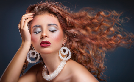 Beautiful young woman with wavy hair and fashion make-up and jewelry Standard-Bild - 119764853