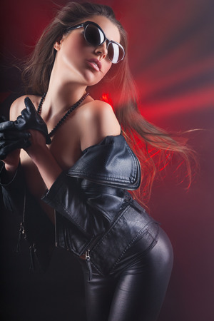 Fashion rocker girl in a leather jacket with sunglasses. Glamour image Stock Photo