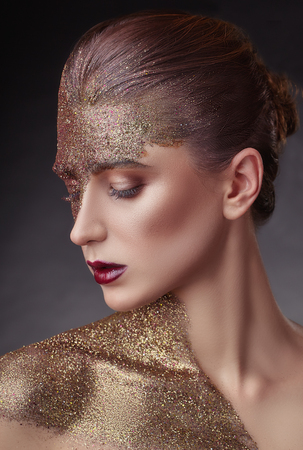 Portrait of a young woman with makeup fashion. Half face and body covered with golden glitter with sparkles