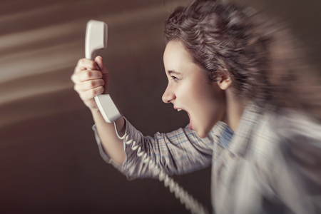 Young girl is screaming into the phone. Blurred background