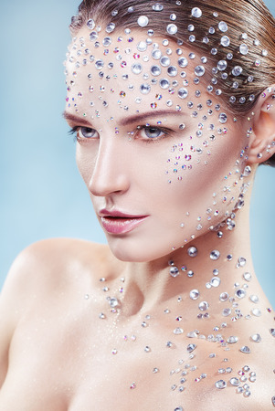 Portrait of a young woman with fashionable make-up with rhinestone on a light background