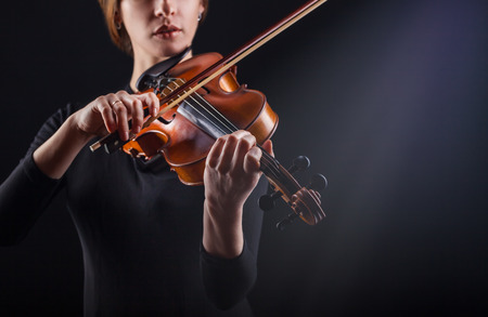 Beautiful young woman playing the violin against a dark background. Focus on violin Standard-Bild - 120933752