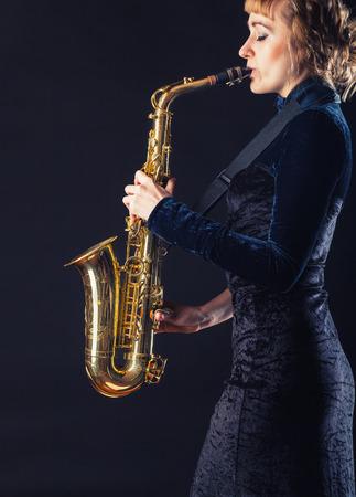Joueur de saxophone. Femme avec saxophone sur un fond sombre Banque d'images