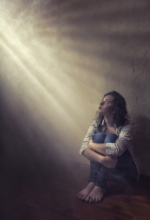 Young sad woman sitting alone on the floor in an empty room in a shadow stripe Standard-Bild - 120934624