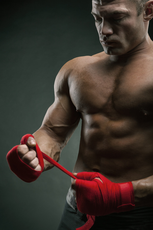 Close-up of a strong boxer putting on red straps and getting ready to fight Standard-Bild - 120934634