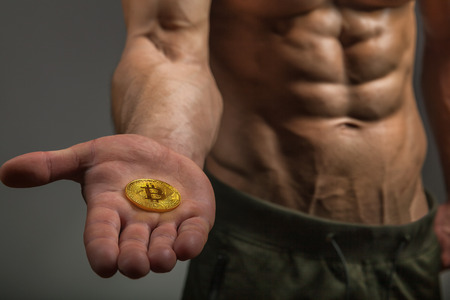 Cryptocurrency golden bitcoin in a strong muscular man hand, digital symbol of a new virtual currency
